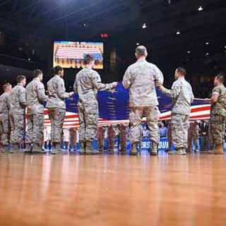 Vets holding flag at basketball game