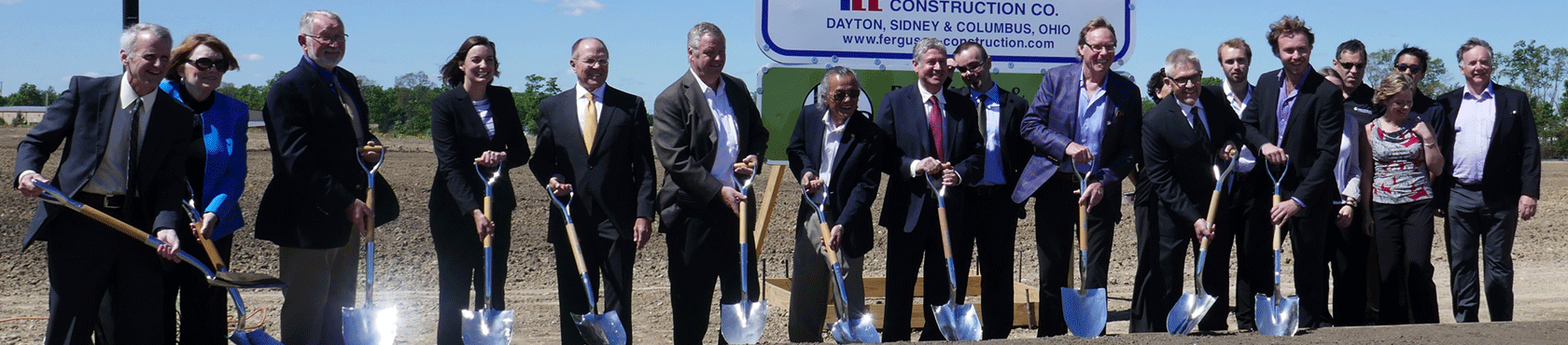 Group posing with shovels at future facility site