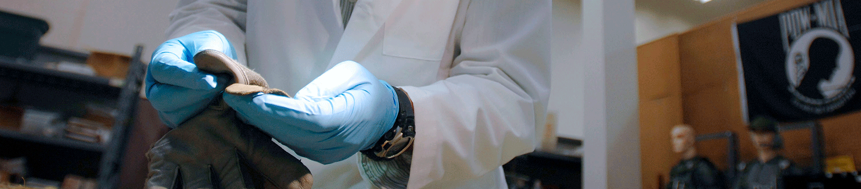Blue gloves holding gray glove under light