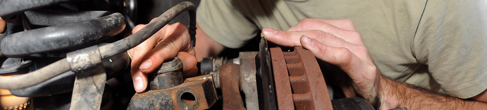 Hands working on automobile suspension